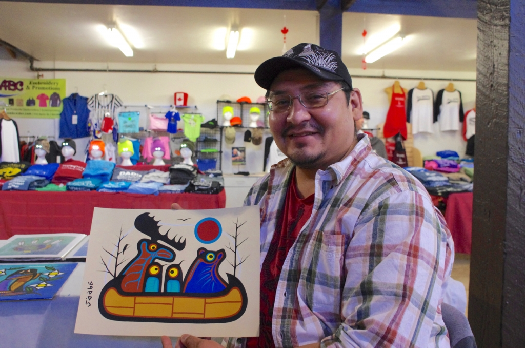 Gull Bay artist Kevin Belmore with his animal protest painting that features a group of animals leaving in a canoe over man's destruction of the environment.  Photo by Rick Garrick